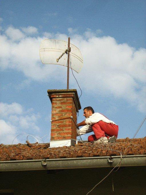 Brane Nikolić na krovu postavlja wifi antenu